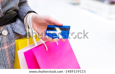 Sale and consumerism concept. Woman with credit card shopping in mall, free space, closeup