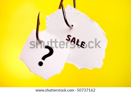 Sale, and question mark on piece of paper on hook