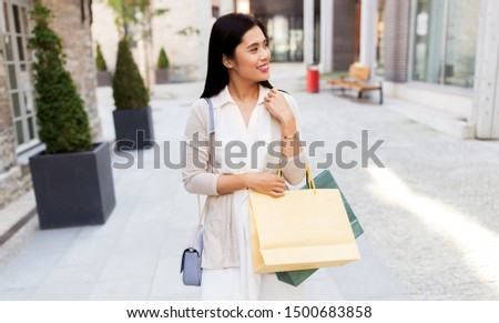 sale, consumerism and jewelry concept - young asian woman with shopping bags and golden bracelet walking along city street