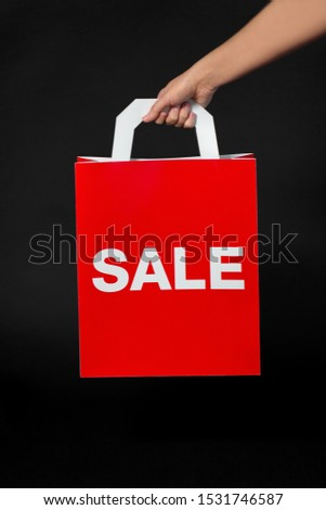 sale, consumerism and outlet concept - hand holding red shopping bag on black background
