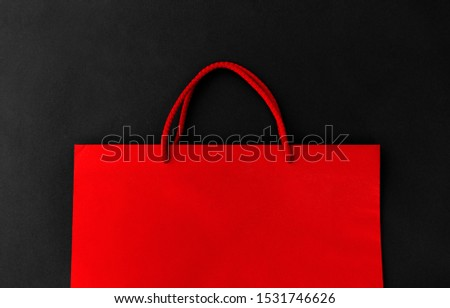 sale, consumerism and outlet concept - red shopping bag on black background