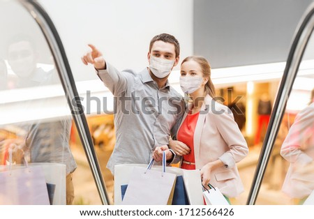 sale, consumerism and pandemic concept - happy young couple wearing face protective medical mask for protection from virus with shopping bags rising on escalator and pointing finger in mall