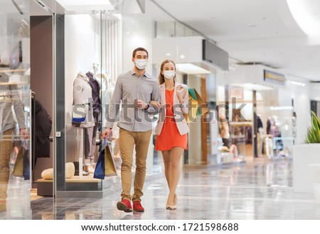 sale, consumerism and pandemic concept - happy young couple wearing face protective medical mask for protection from virus disease with shopping bags walking in mall