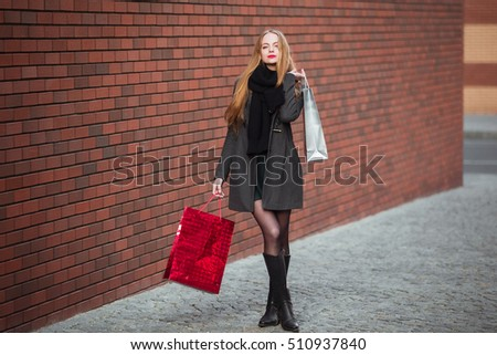Sale, consumerism and people concept - happy young beautiful women holding shopping bags, walking away from shop. #510937840