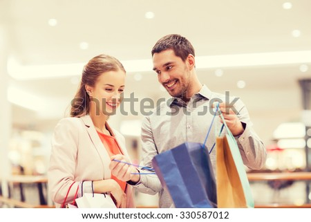 Shutterstock sale, consumerism and people concept - happy young couple showing content of shopping bags in mall
