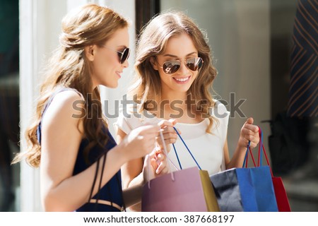 Shutterstock sale, consumerism and people concept - happy young women looking into shopping bags at shop window in city