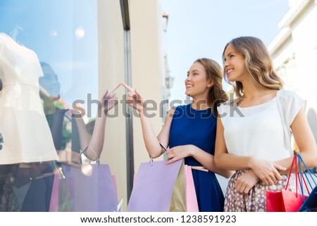 sale, consumerism and people concept - happy young women with shopping bags pointing finger to dress at storefront