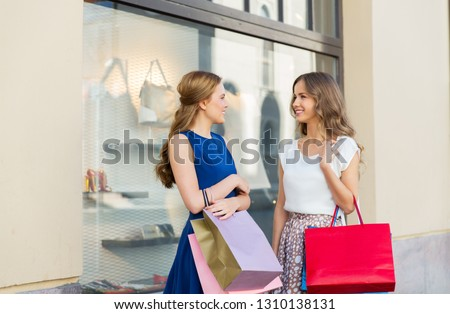 sale, consumerism and people concept - happy young women with shopping bags talking at storefront