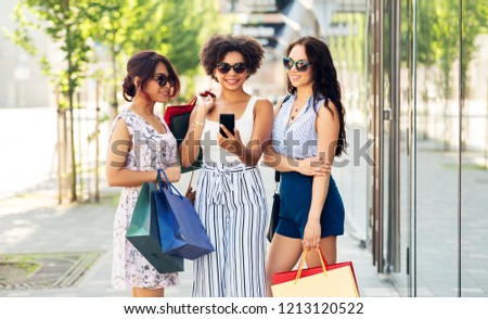 sale, consumerism and people concept - happy young women with smartphones and shopping bags on city street