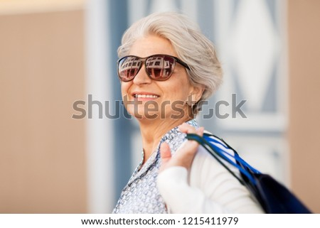 sale, consumerism and people concept - senior woman in sunglasses with shopping bags in city
