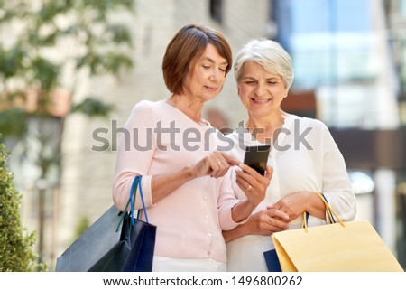 sale, consumerism and people concept - two senior women or friends with shopping bags and smartphone on tallinn city street