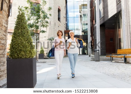 sale, consumerism and people concept - two senior women or friends with shopping bags drinking takeaway coffee and walking along tallinn city street