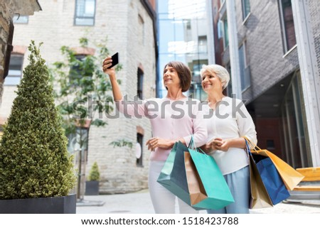 sale, consumerism and people concept - two senior women or friends with shopping bags taking selfie by smartphone on tallinn city street