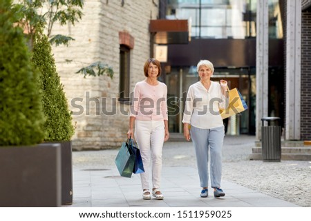 sale, consumerism and people concept - two senior women or friends with shopping bags walking along tallinn city street