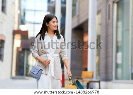 sale, consumerism and people concept - young asian woman with shopping bags walking along city street