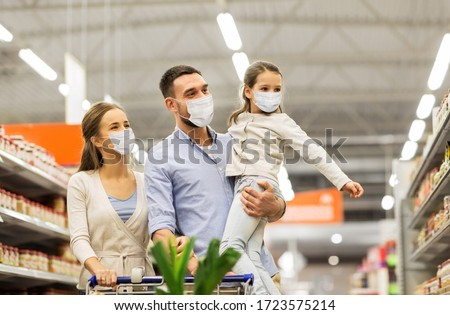sale, family and pandemic concept - happy mother, father and little daughter wearing face protective medical masks for protection from virus disease with shopping cart buying food at supermarket