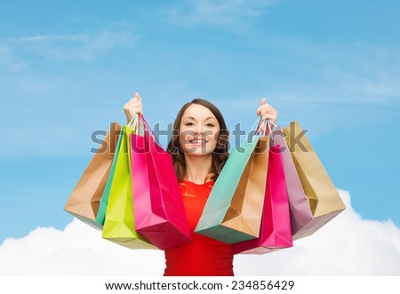 sale, gifts, holidays and people concept - smiling woman with colorful shopping bags over blue sky and white cloud background