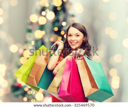 sale, gifts, holidays and people concept - smiling woman with colorful shopping bags over living room and christmas tree background