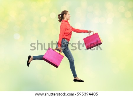 sale, motion and people concept - smiling young woman with shopping bags running in air over summer green lights background #595394405