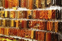 Sale of amber beads of different colors, sizes and shapes in the display case. Sun stone from ancient petrified resin. Jewelry made from natural amber mineral. Fashionable women's jewelry. Show-window