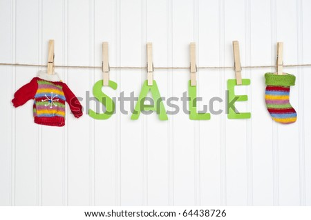 SALE on a Clothesline with Warm Winter Clothing.  Holiday Concept.
