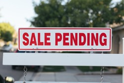 Sale Pending real estate sign by a newly listed house.