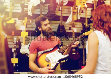 sale, people, musical instruments and entertainment concept - assistant showing electric guitar to customer at music store over lights
