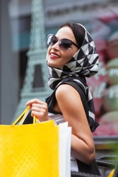 Sale. Portrait of happy young woman wearing sunglasses and black and white handkerchief sitting in the cafe with a lot of shopping bags. Copy space for text. Paris background. Eiffel Tower background