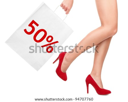 Sale rebate shopping bag. Shopper showing 50% rebate sign on shopping bag walking with sexy legs and red high heels. Isolated on white background.