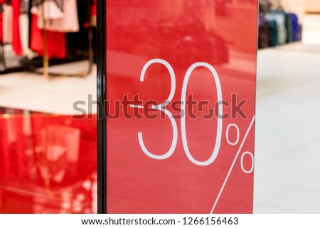 Sale. Shop window with 30 percent discount. Winter sale. Window shop with dressed mannequin, text Sale and 30 percent discount.Seasonal discounts in the store.New Year discounts.The final sale at a