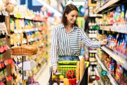 Sale, Shopping, Consumerism And People Concept. Smiling young woman standing with trolley basket full of eco bio products, walking near shelves at grocery store, choosing healthy food in market