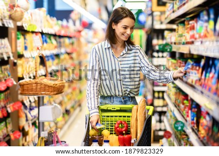 Sale, Shopping, Consumerism And People Concept. Smiling young woman standing with trolley basket full of eco bio products, walking near shelves at grocery store, choosing healthy food in market Foto d'archivio ©