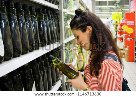 Sale, shopping, consumerism, people concept. Woman shopping and choosing food products in supermarket. Financial management with economic foods. Trying to find the best in terms of price and quality.