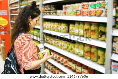Sale, shopping, consumerism, people concept. Woman shopping and comparing food products in supermarket. Financial management with economic foods. Trying to find the best in terms of price and quality.