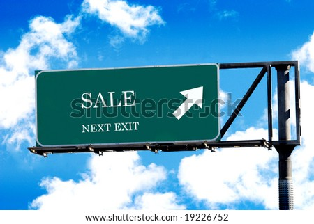 sale sign on freeway signpost and blue sky