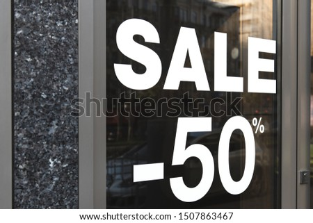 Sale sign on the glass of a retail store. White color coated sticker. Text minus fifty percent seasonal offer. Special offer. #1507863467