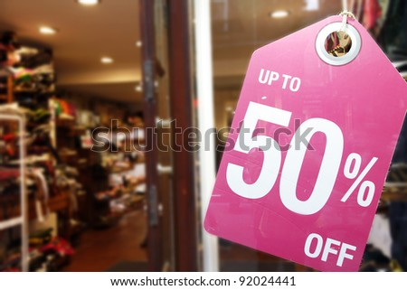 Sale signs in shop window, big reductions