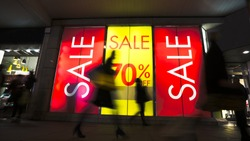 Sale signs in shop window, include silhouette of shoppers