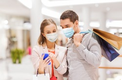 sale, technology and pandemic concept - happy young couple with shopping bags and smartphone wearing face protective medical mask for protection from virus disease in mall