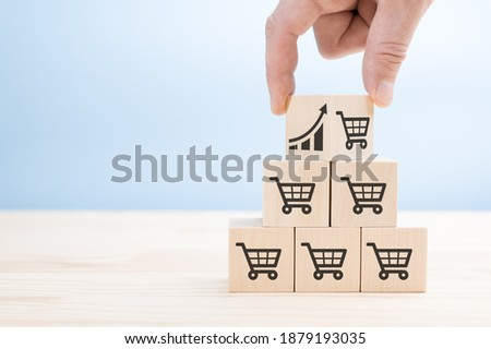 Sale volume increase make business grow concept. businessman's hand turns over the top cube of the sales pyramid. Flips cube with icon graph and shopping cart symbol. Foto stock ©