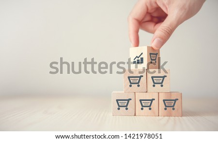 Photo of  sale volume increase make business grow,  Flips cube with icon graph and shopping cart symbol.