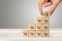 Sale volume increase to make a business grow,  wooden cube with shopping cart symbol.