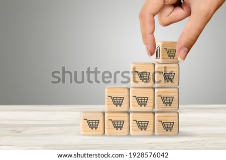 Sale volume increase to make a business grow,  wooden cube with shopping cart symbol. Foto stock ©