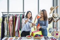 Sale woman showing a neckless to a woman shopper holding shopping bags at a clothing fashion shop.