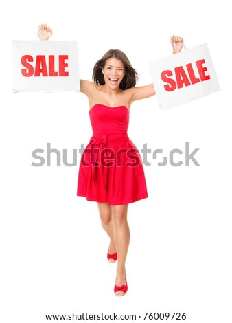 Sale - Woman showing shopping bags with sale written on them. Excited and cheering mixed race Chinese Asian Caucasian female model in red summer dress isolated on white background in full length.