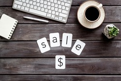 Sale word , dollar sign, keyboard, notebook, coffee on wooden office desk background top view
