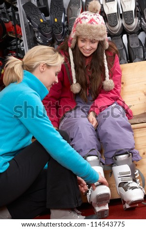 Sales Assistant Helping Teenage Girl To Try On Ski Boots In Hire Shop