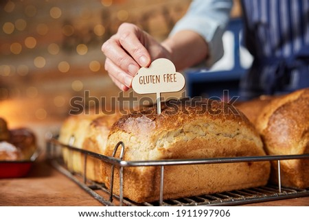Sales Assistant In Bakery Putting Gluten Free Label Into Freshly Baked Baked Sourdough Loaves Of Bread Foto stock ©