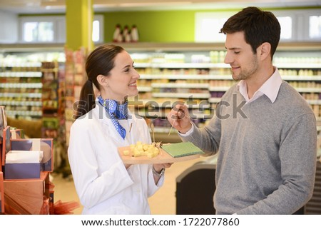 Sales assistant offering customer cheese in an organic grocery store