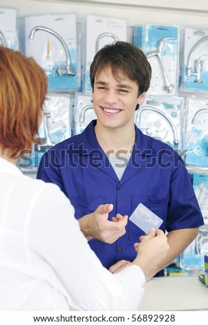Sales clerk receiving  credit card  for payment  in DIY store - stock photo